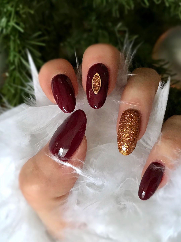 Nail art voor kerst met donker rood, goud en gouden amulet.